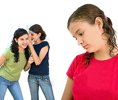 two young girls laughing behind another girls back